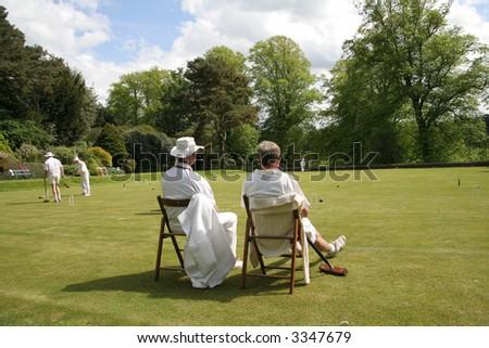 Two gentlemen sit watching a croquet match
