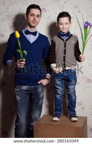 Two gentlemen: young father and his little cute son. man is holding yellow tulip. blue-eyed boy with purple flower. Studio shot