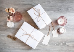 Two gift boxes in white wrapping paper on wooden table with two blank gift tags and candles. Wrapping paper and tags print mockup.