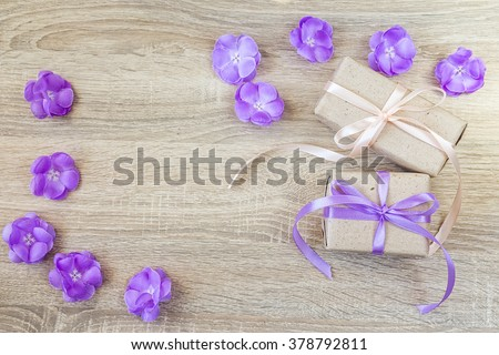 Two gift boxes, purple flowers on wood background with empty space for text. Top view with copy space