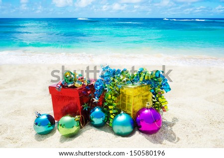 Two gift boxes with Christmas balls on sandy beach in sunny day- holiday concept