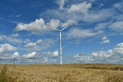 Two Gigantic electric wind turbines aligned in the middle of the fields in Flanders near tongeren.