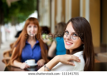 two girl friends drinking coffee at breakfast or dinner at an outdoor cafe