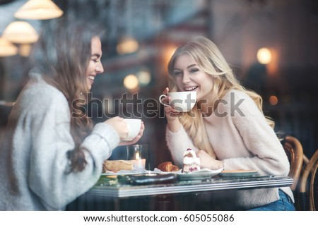 Two girl friends drinking coffee in the cafe #605055086