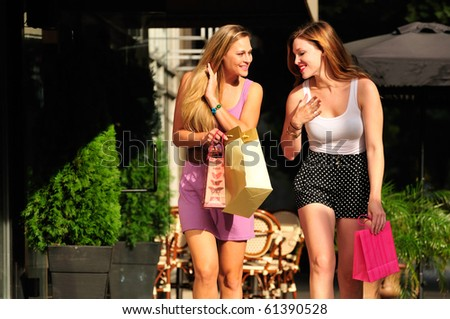 two girl friends having fun on a shopping spree in the city