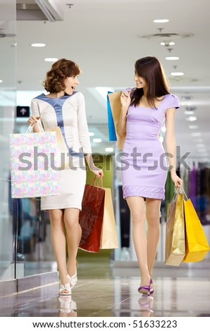 Two girl-friends on shopping walk on shopping centre with bags