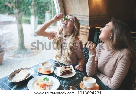 Two girl friends spend time together drinking coffee in the cafe, having fun by breakfast and dessert.