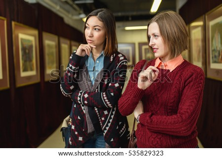 Two girl friends standing in a gallery contemplating and discuss paintings artworks displayed on gallery walls #535829323