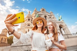 Two girl friends take a selfie against the background of the Sacre Coeur Basilica on Montmartre hill. Travelling to France together