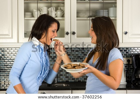 Two girl friends tasting homemade cookies in the kitchen #37602256
