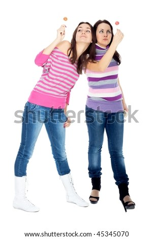 Two girl friends with lollipop smiling isolated on white