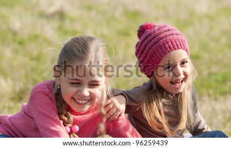 Two girl on a lawn. Little girl with her older sister laughing