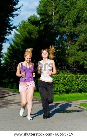 two girl runs in park