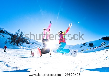 two girl snowboarders having fun