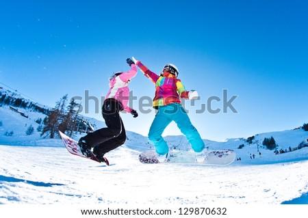 two girl snowboarders having fun