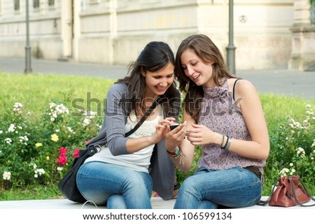 Two Girl While They Make a Speak a Phone