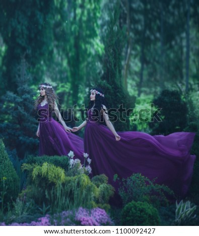 Two girlfriends, a blonde and a brunette, are holding hands. Background beautiful flowering garden. The princesses are dressed in luxurious purple dresses. Long, wavy hair with floral wreaths