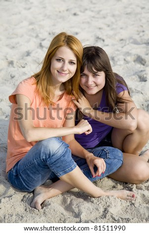 Two girlfriends at sand.