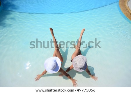 Two girlfriends enjoying the sun in a swimming pool on vacation or holiday