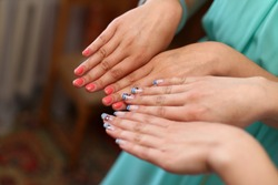 two girlfriends girls show each other hands and fingers, comparing manicure and showing off a new beautiful nail varnish