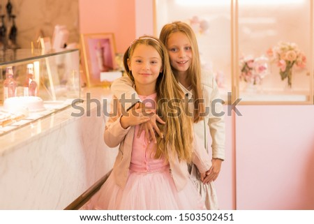 Two girlfriends in a cafe by the window with a cake. Girlfriend in a store. #1503502451