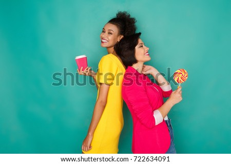 Two girlfriends in colorful clothes at blue background. African-american and caucasian women having fun, holding coffee and lollipop, offering candy to friend. Sharing, multiethnic friendship concept