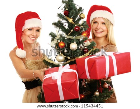Two girlfriends in santa hat near Christmas tree with gift box on a white background.