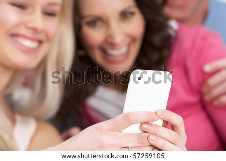 Two Girlfriends Looking At Pictures On phone At Home