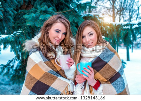 Two girlfriends of the girl get warm covered with a warm blanket and a veil. In their hands they hold mugs tea and coffee. Women sisters are warmed by cold winter weather. #1328143166