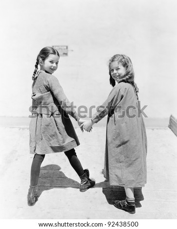 Two girlfriends walking and holding hands Zdjęcia stock ©
