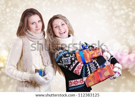 Two girlfriends with christmas presents: disappointed - one and happy smiling - other