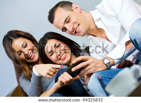 two girls and a boy having fun with a mobile phone on the couch at home