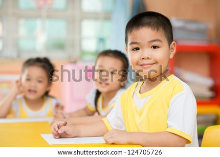 Two girls and a boy sitting behind the desk