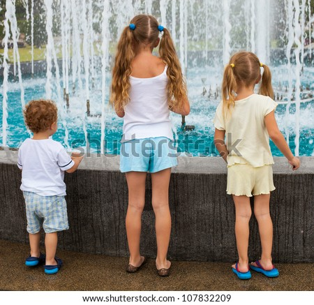 two girls and a little boy standing near the fountain back to the camera