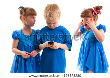 Two girls and boy are playing on his cell phones on white background. Children have a conflict over the phone. The girl was crying. A boy playing a game on the phone. They dressed in blue.