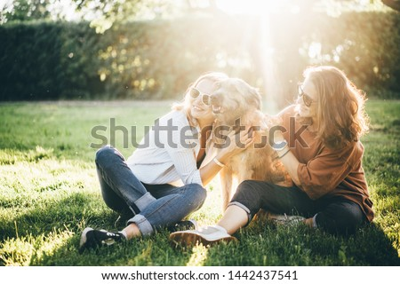 Two girls and dog relaxing in the park at the sun set. And enjoying time together