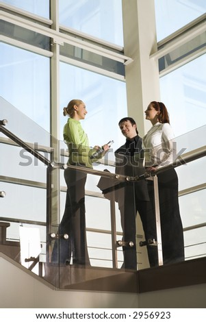 Two girls and man are talking in the building with glassy walls