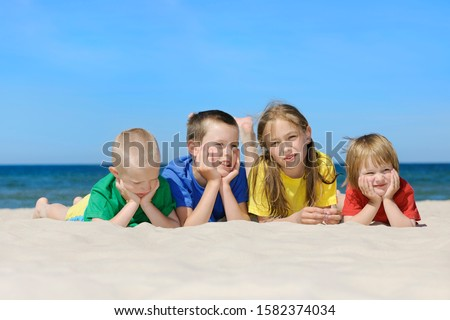 Two girls and two boys in colorful t-shirts lying on sandy beach, blue sky in the background #1582374034