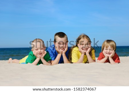 Two girls and two boys in colorful t-shirts lying on sandy beach, blue sky in the background #1582374067