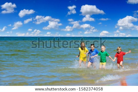 Two girls and two boys in colorful t-shirts running on a sandy beach, blue sky white clouds in the background #1582374058