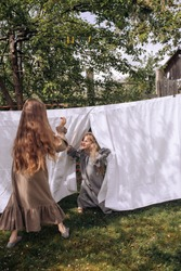 Two girls are playing hide and seek outdoors in country side among white sheets, wearing retro night gowns, two sisters playing, selective focus