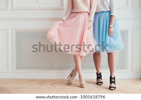 Two girls are posing for a photo. They are showing their legs, folding skirts a wearing high heels. Celebration of the party.
