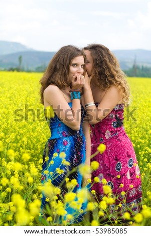 Two girls are secretive in a yellow field