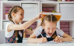 Two girls are sitting at one desk in the classroom. One girl hits another on the head. The problem of bullying at school and the aggression of children concept.