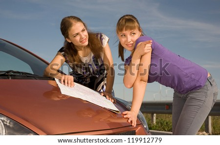 Two girls are standing by the car with the map and one of them is showing the direction