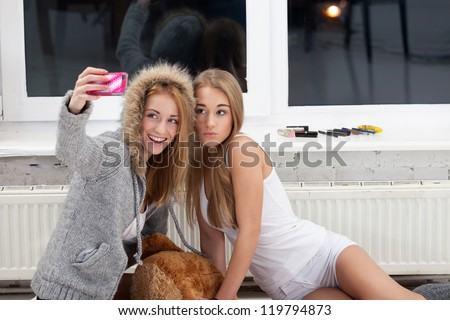 Two girls are taking picture with mobile phone to publish it in social network