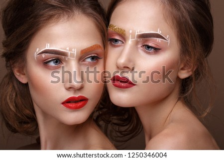 Two girls are twin sisters with an unusual eyebrow makeup. Beauty face. Photo taken in the studio.