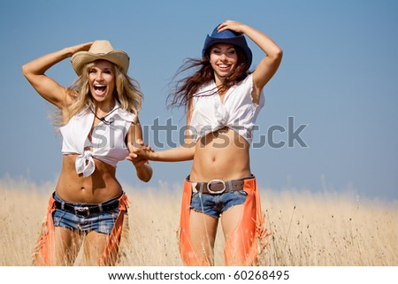 Two girls are walking at the field. Young women in costumes of cowboys outdoors
