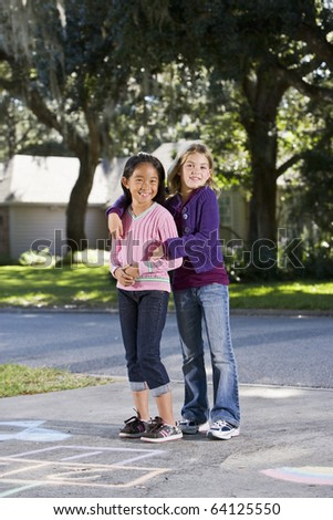 Two girls at home on driveway standing in front of hopscotch board (7 years)
