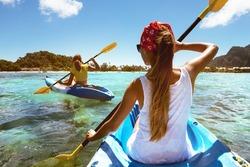 Two girls at sea kayaks or canoe at tropical beach. Travel or kayaking concept